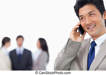 Smiling businessman on his mobile phone and team behind him