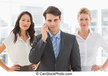 Smiling businessman on the phone in front of his team