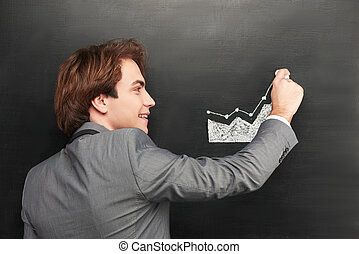 Smiling businessman painting graph on chalkboard