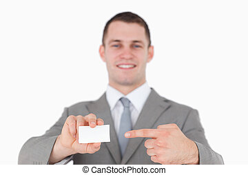 Smiling businessman pointing at a blank business card
