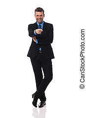 Smiling businessman pointing at camera side