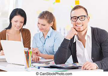 Smiling businessman. Portrait of thoughtful young man with executives working in background