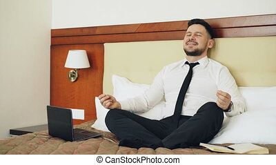 Smiling businessman put off laptop computer and taking yoga lotus position sitting relaxed on bed in hotel room. Travel, business and people concept