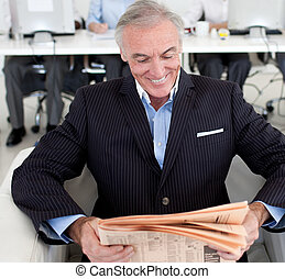 Smiling businessman reading a news