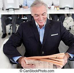 Smiling businessman reading a news