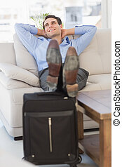 Smiling businessman relaxing on couch with feet up on suitcase