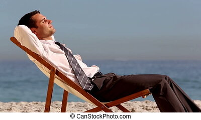 Smiling businessman relaxing on the beach