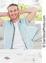 Smiling businessman relaxing with hands behind head