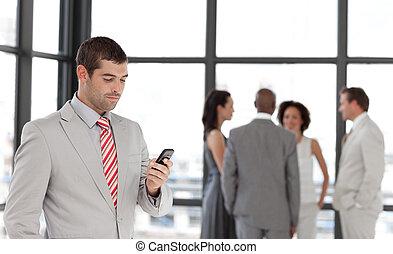 Smiling Businessman sending a text message