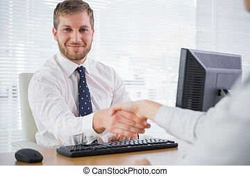 Smiling businessman shaking hands with a co worker and looking at camera at his desk in office