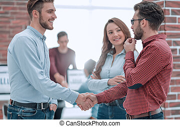 Smiling businessman shaking hands with colleague in office.