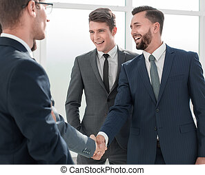 smiling businessman shaking hands with his partner