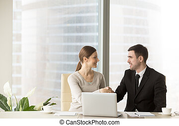 Smiling businessman shaking hands with businesswoman in office,