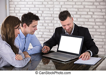 Businessman Showing Laptop To Couple