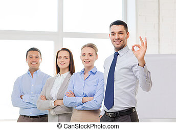 smiling businessman showing ok-sign in office - office,...