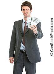 Smiling businessman showing packs of dollars