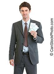 Smiling businessman showing packs of euros