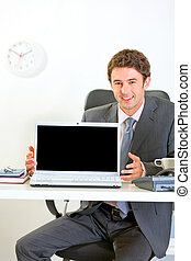 Smiling businessman sitting at office desk and showing laptops blank screen