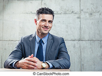 Smiling businessman sitting at the table