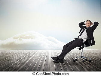 Smiling businessman sitting in a swivel chair on wooden ...