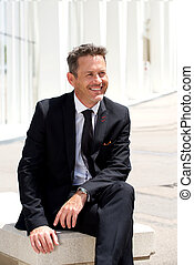 Smiling businessman sitting in suit and tie