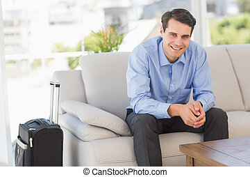 Smiling businessman sitting on couch waiting to leave on business