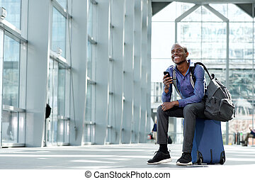 smiling businessman sitting on luggage at airport with cell phone