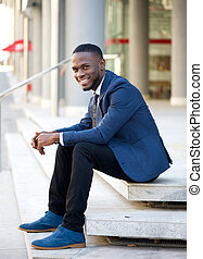 Smiling businessman sitting outdoors on steps