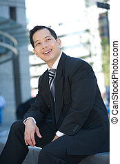 Smiling businessman sitting outdoors