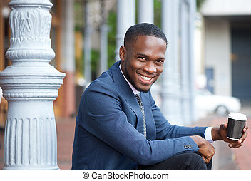 Smiling businessman sitting outdoors with cup of coffee