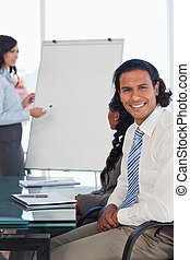 Smiling businessman sitting with hands crossed while listening to a presentation