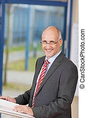 Smiling Businessman Standing At Podium