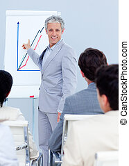 Smiling businessman standing in front of his team