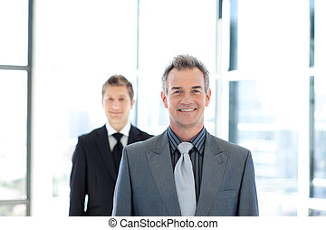Smiling businessman standing in front of the camera