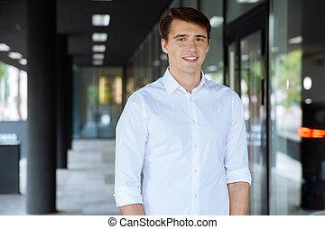 Smiling businessman standing near business center