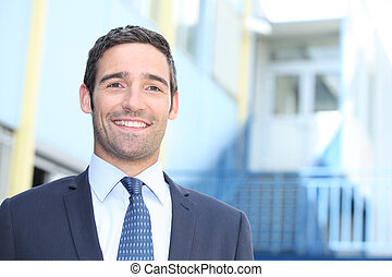 Smiling businessman standing outside a building on a sunny day