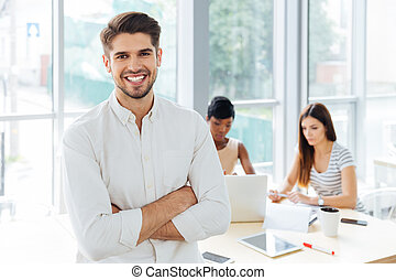 Smiling businessman standing with arms crossed in office