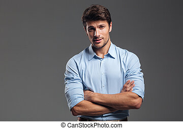 Smiling businessman standing with arms folded