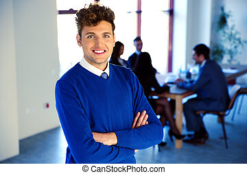 Smiling businessman standing with arms folded in front of colleagues