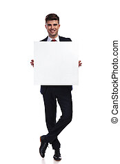 smiling businessman standing with legs crossed holds white empty board