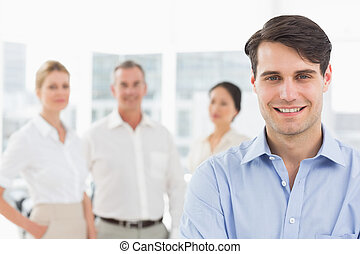Smiling businessman standing with team behind him in the ...