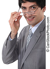Smiling businessman taking off his glasses
