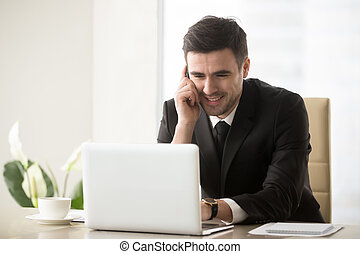 Smiling businessman talking on phone sitting at workplace near l