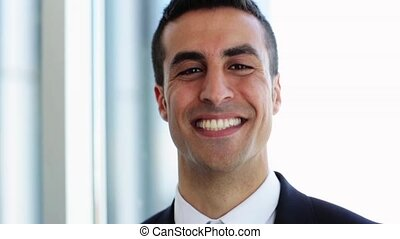 smiling businessman touching his hair at office - business,...