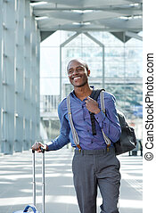 smiling businessman traveling with bags