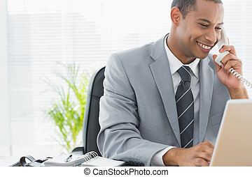 Smiling businessman using laptop and phone