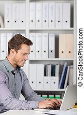 Smiling Businessman Using Laptop At Desk