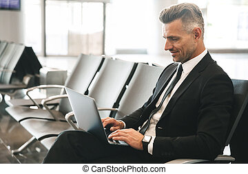 Smiling businessman using laptop computer