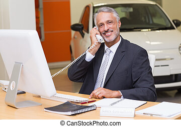 Smiling businessman using laptop on the phone