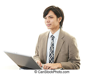 Smiling businessman using laptop